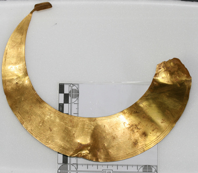 Image of a crescent shaped sheet of gold metal with some geometric engravings