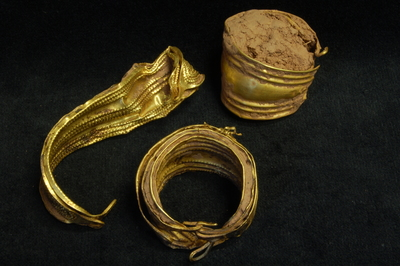 Image showing three groups of gold bracelets, plugged with mud