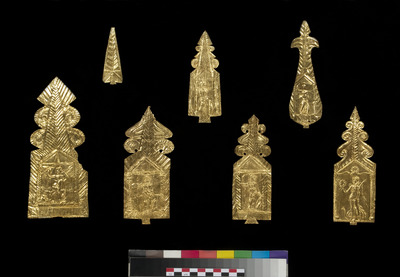 Photograph of seven thin sheets of gold stamped with images of a figure holding a shield and spear