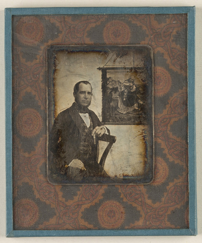 Portrait of a men, seated, resting his left arm on a backrest, holding a cigar. A tapestry with a figural motive is hanging on a wall behind him.