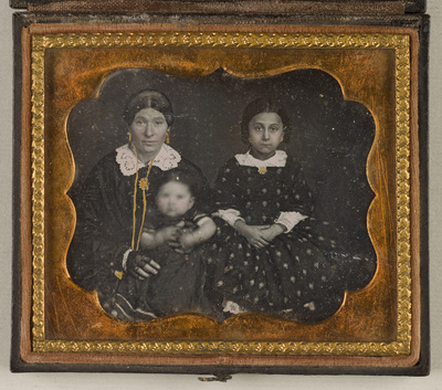 Group portrait; a woman seated on the left is holding a baby. Next to her on the right is sitting a girl wearing dotted dress. All faces are coloured in pink, pieces of the women´s jewellery are lavishly painted in gold. Face and hands of the baby are blurred.