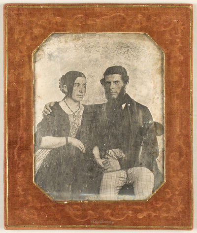 Portrait of a young couple, seated. The man, wearing checked trousers, is holding woman around her shoulder. The woman is pregnant.