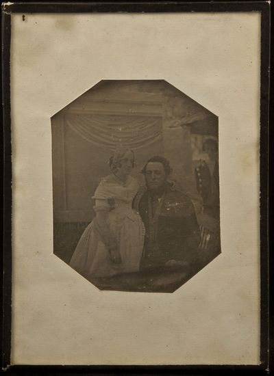 Portait of a young coulpe, taken outside, in front of an illusive background (drapery), in the back on the right standing a man wearing livery
