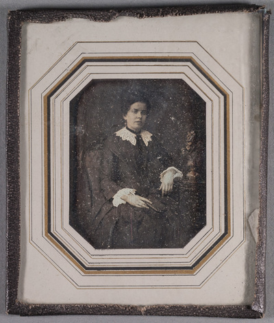 Portrait of Maria Helena Adelaide Kekoni (19.2.1835) sitting in a chair with a book in her left hand. Flowers on the side table.