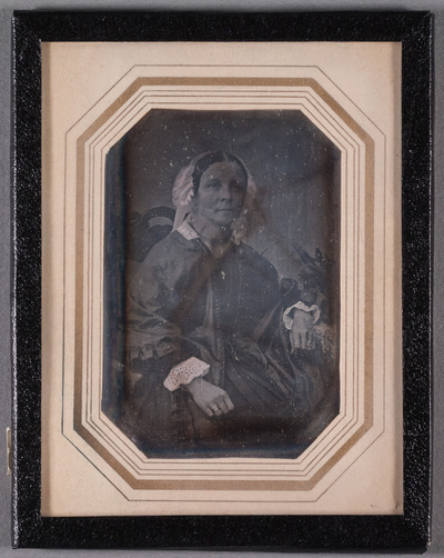 Portrait of a married woman sitting on a chair. Flowers on a side table.