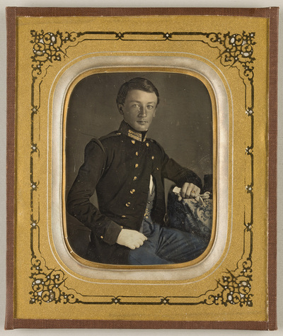 Portrait of a young man in uniform, seated, resting his left arm on a table, in left hand holding a white glove. The tablocloth is decorated with floral and ornamental motif.