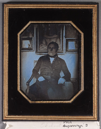 Portrait of Director Anton Jaenisch (1800-1861) sitting on a chair,  paintings on the wall on the back ground.