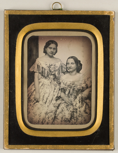 Portrait of two young ladies in lavishly decorated dresses with flower motif; in the back on the left hanging dark curtain