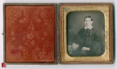Seated woman with her arm resting on cloth covered table and holding a book or a daguerreotype case with her right hand