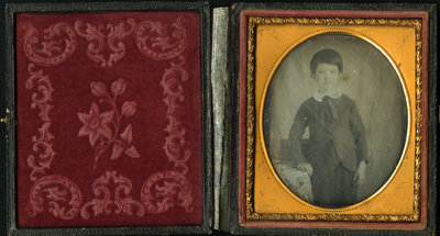 Three quarter length frontal portrait of standing schoolboy leaning at table with decorative cloth. Image is very damaged.