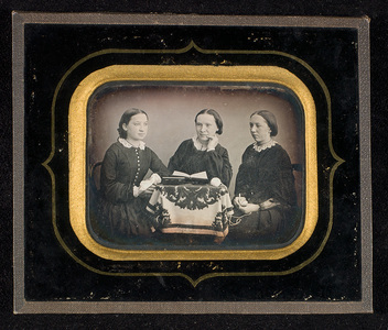 Portrait of three young women seated around a table.