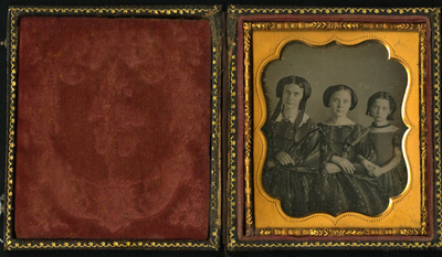 Three quarter length frontal portrait of three of young ladies, probably sisters posing in order of age. The eldest two wear formal dresses with identical printed pattern. The youngest has a simple frock and a necklace. Their hands are folded and linked.