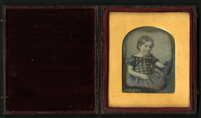 Half length portrait of seated child facing right with short blond hair. She wears a checked tartan frock. She holds a box (?) or bag in her left hand.