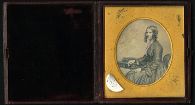 Seated three quarter length portrait of young lady facing left. Elaborate dress with decorative sleeves and bracelets. Curled side locks. Right arm resting on elegant table with two books.