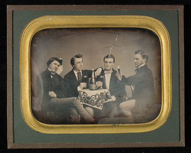 Portrait of four young men seated around a table with tablecloth. On the table is an opened bottle of wine. They all have a glass of wine in their hand. Celebrating graduation?