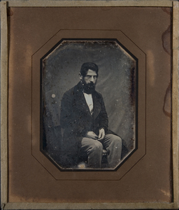 Portrait of beared man with hands on his lap