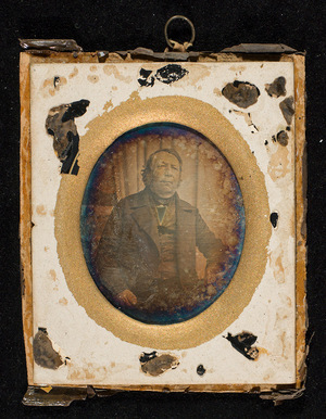 The glass is missing. A small piece of the painting from the glass is present on the paper mat. Indicating that the glass was painted black and gold, with a gilded border. The plate is corroded.