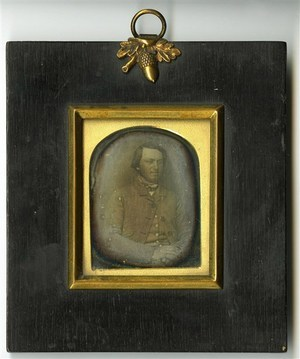 Plate is mounted in a wood frame. Top margin decorated with an acron in brass