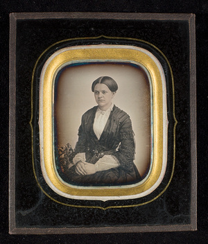 Portrait of a woman, seated, hands on her lap. The portrayed is Thea Ruback.