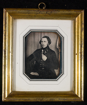 Portrait of a man, half figure, seated with his left arm leaning against a table and the hand in his waistcoat. In the background to the right a drapery with a pattern.