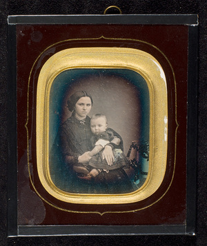 Portrait of a seated woman with a baby on her lap. The woman is Sofie Grieg.