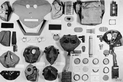 Black and white image showing a range of objects used in the manufacture of gas masks including cloth masks, respirators and similar