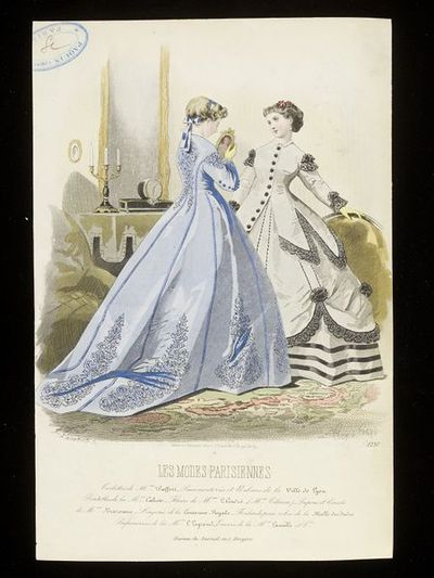 François-Claudins Compte-Calix and Lacouriere. Two day dresses by Mme Pieffort. Les Modes Parisiennes, mid 1860s. Two women in an interior. To the left, a woman in a Princess line dress in blue silk, the individual panels of the dress braided and embellished, the seams outlined with darker blue binding. She holds a framed portrait in her hands. To the right, a grey dress trimmed with black lace, the jacket bodice with long peplums over a looped-up overskirt and black-striped underskirt. The women in an interior with a black and gold clock and candlestick on a mantelpiece in the background.