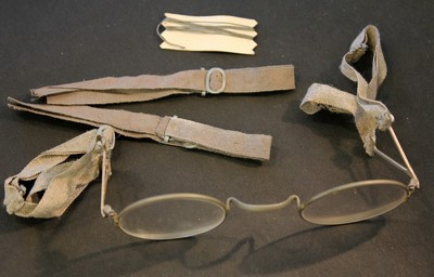 A pair of spectacles with shortened arms attached to canvas tape that can be looped around the ears