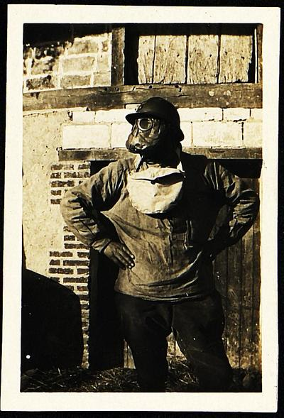 Sepia-toned photograph of a man wearing a gas maks and posing with his hands on his hips