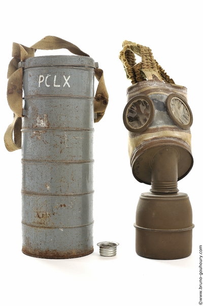 A cylindrical gas mask with a large brown metal breathing snout and its grey metal case.
