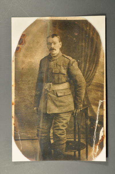 Faded and torn sepia-toned photograph of a man with a moustache posing in military uniform