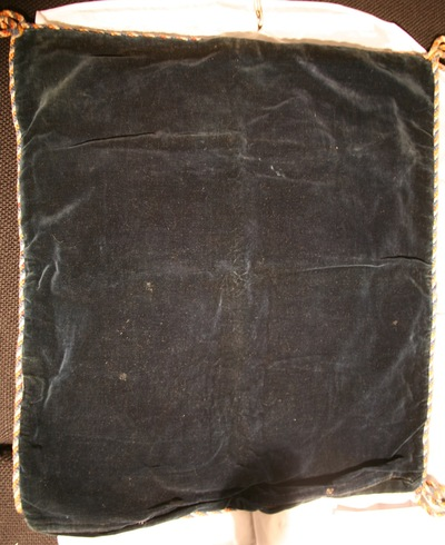 A black cushion cover possibly made of velvet, with a multicoloured band around the edge.
