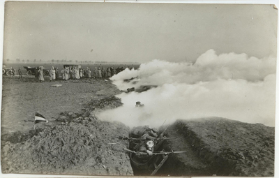 A photograph showing soliders crouched in a trench running down the centre of the photograph, wearing gas masks as a gas cloud coming from the right envelopes them. In the background, a line of officers watch.
